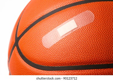 This is a close up photo of a basketball with a band-aid. Shot on a white background. Sports injury concept.