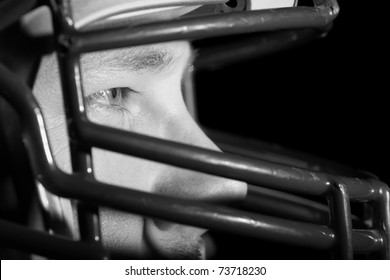 This is a close up, high contrast black and white image of a young man wearing a football helmet and looking away from the camera with an intense look in his eye.