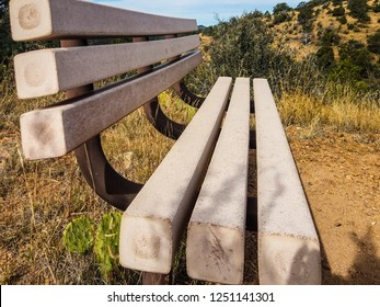 This is a close up view of one of the Thumb Butte benches on top of the Thumb Butte Trail in the Prescott National Forest in Prescott, AZ. The Thumb Butte formation is seen in the background.