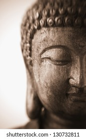 This is a close-up photograph of an antique wood carving of a sculpture of Buddha with focus on the downcast eye. The sepia image was taken with a Lensbaby and has a very shallow depth of field.
