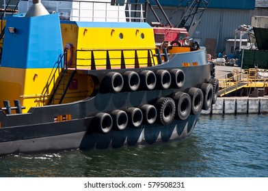 This is a closeup of a yellow and blue tug boat, with tires lining the sides.