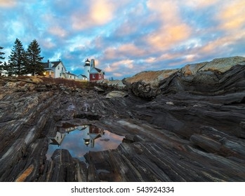 This is a cloudy sunrise at Pemaquid Point in Bristol, Maine.  A reflection of the lighthouse can be seen in a puddle.