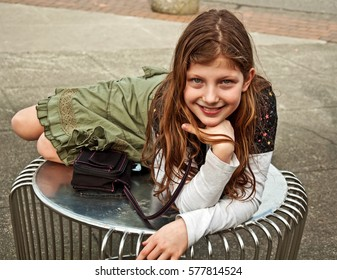 This cute 9 year old Caucasian girl is outdoors curled up on a street table and smiling.