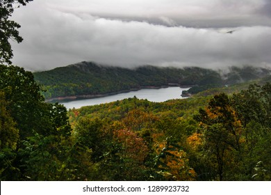 This is a distant shot of Fontana Lake near Bryson City, NC, in the Nantahala NF in NC. Autumn tree colors surround Fontana Lake, with low storm clouds blanketing the background mountains.