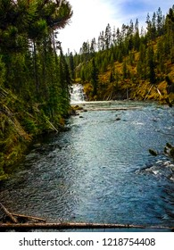 This is a distant view of Lewis Falls in Yellowstone National Park in Wyoming. It is approximately 30 feet in height, and can be seen from the road at a distance.