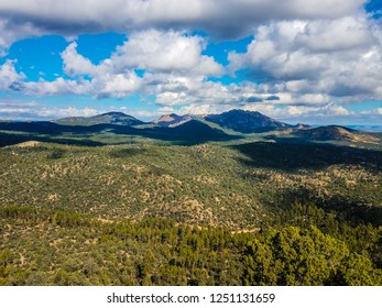 This is a distant view while ascending the Thumb Butte Trail in the Prescott National Forest in Prescott, AZ. Mountain peaks are in the background.