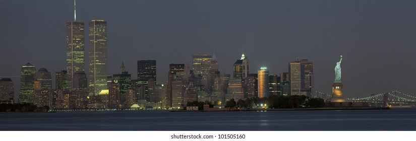 This is the downtown Manhattan skyline and Statue of Liberty. It is the view at dusk. The World Trade towers dominate the left hand side, the Statue of Liberty is on the right.