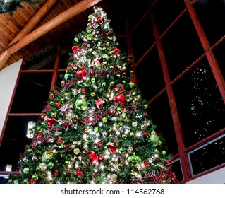 This dramatic image is of a very large indoor Christmas tree with lights, ornaments, balls, square gifts and more reflected against sectioned windows against a night sky.