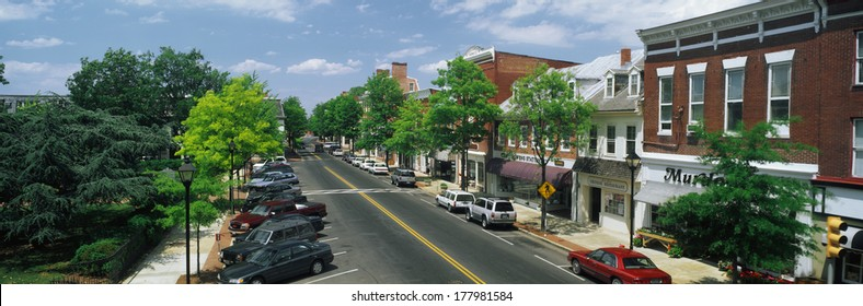 This is the Eastern Shore of Maryland. It typifies small town America or Main Street USA. We see shop fronts on a tree lined street. Cars  are parked in front of shops on either side of the street.