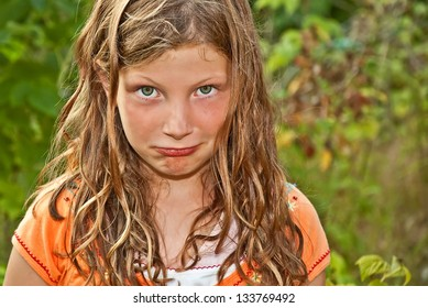 This elementary aged Caucasian girl is playing outdoors and making a goof pouty face.  Her hair is tangled and wind blown, and she has piercing green eyes.