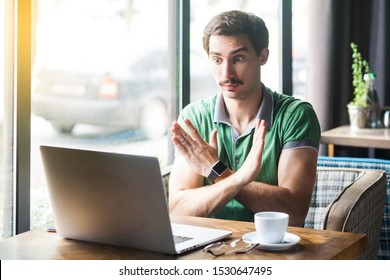 This is the end. Young serious businessman in green t-shirt sitting and looking at laptop screen on video call, showing closed or x sign with hand. business concept. indoor shot near window at daytime