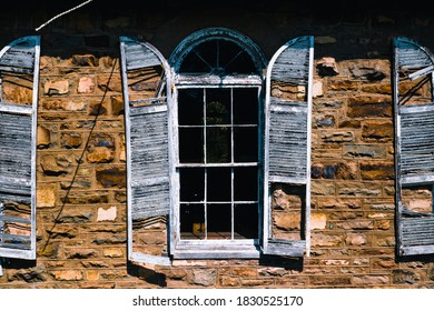 This is an exterior view of derelict wood shutters and windows against sandstone at the abandoned Rising Zion Baptist Church in rural Virginia.