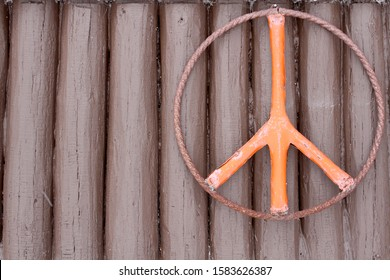 This is the exterior wall of a brown log cabin with a peace symbol hanging on it.  The logs are vertical, rustic and old looking.  This cabin was built in Minnesota during 1925 from cedar logs.