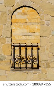 This is fake window with forged lattice. This is yellow stone wall with false window.