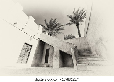 In this filtered monochrome image, stairs lead to the roof from the courtyard of a restored traditional arabian house with carved wooden doors and palm trees.