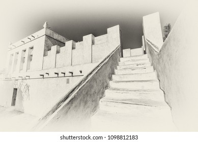 In this filtered, monochrome image, stairs lead to the roof from the courtyard of a restored traditional arabian house.