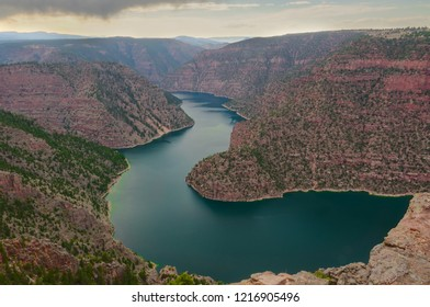 This is the Flaming Gorge Reservoir in the Flaming Gorge National Recreational Area in Utah.  The walls of this gorge are extremely steep, and mountains are seen in the distance.
