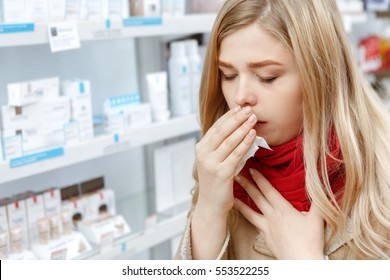 This flu is getting to her. Young woman coughing covering her mouth with a tissue buying medications at the pharmacy copyspace cough coughing sick ill cold flu seasonal healthcare people concept
