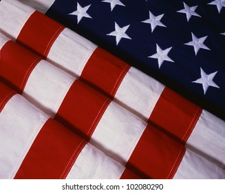 This is a folded American flag. The field of stars is folded in the shape of an uneven triangle while the field of stripes is folded over themselves and comes out from the stars diagonally.