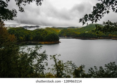 This is Fontana Lake in the Nantahala National Forest in western North Carolina. There are numerous coves on this lake with the forest and Autumn colors surrounding it. Low storm clouds hug mountains.
