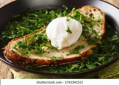 Recette pour cette soupe de pain grillée Acorda avec gros oeuf poché dans une assiette sur la table. horizontal