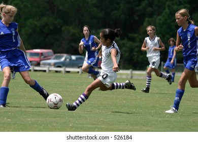 This girl forward has a great line to the soccer ball to provide a vital kick downfield to advance her team
