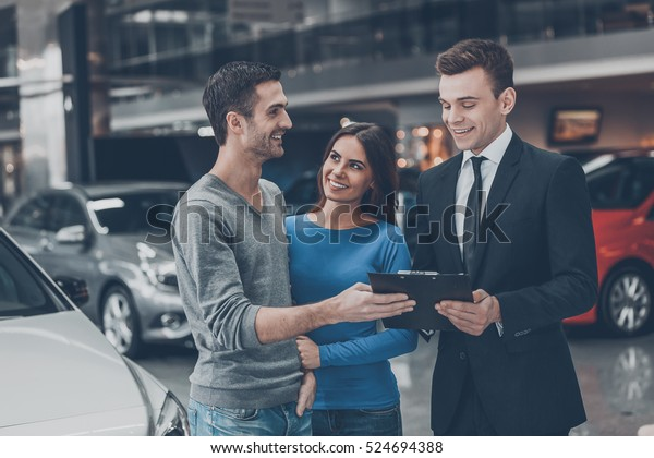 This is good choice. Confident young salesman making deal with young couple