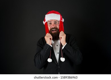 This hat warms his ears. Happy businessman wear santa hat. Bearded man smile in hat with earflaps and faux fur. Fashion accessory for Christmas. Warm and stylish trapper hat for santa party.