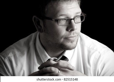 This is a high contrast black and white shot of a businessman thinking with a worried look on his face. Shot on a black background.
