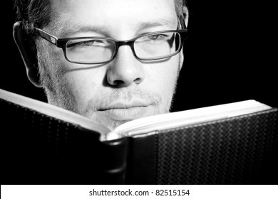 This is a high contrast black and white image of a man with glasses reading a book. Shot with a hard light on a black background.
