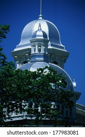 This is the historic State Capitol Building. It has two silver domes with a green-leafed tree in front of the round shaped dome.
