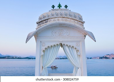 This is a horizontal, selective focus shot of a boat ride on Lake Pichola. This was shot at dusk from a viewpoint at the Island Palace in Udaipur, India. The lake shore is seen beyond.