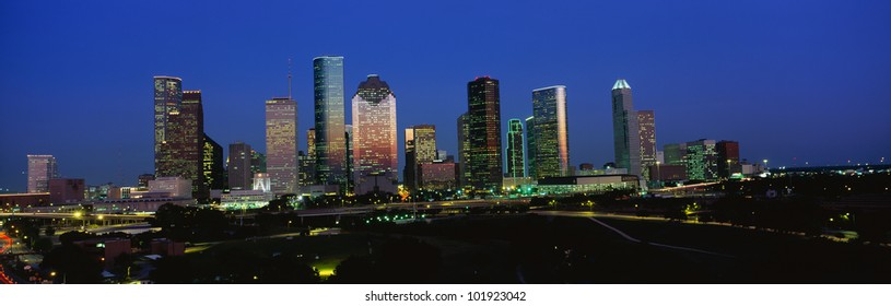This is the Houston skyline at sunset with Memorial Park in the foreground.