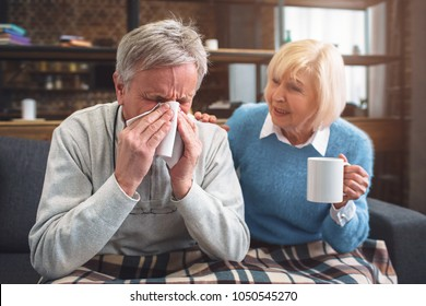 This ill man is sneezing into the napkin. His wife is sitting besides him and advising to drink hot tea from the cup. She is caring about her husband.