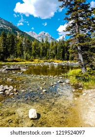 This image was captured at a cove along the Leigh Lake Trail in Grand Teton National Park in Wyoming.There are lots of rocks along the shoreline, and a beautiful view of the mountains.