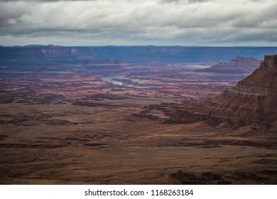 This image was captured at the Needles Overlook near Monticello, Utah on a stormy day. A steep cliff on the right leads the viewer to the Colorado River down below in the center.