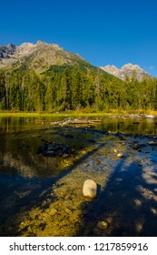 This image was captured on the Leigh Lake Trail in Grand Teton National Park in Wyoming. Lots of rocks and shadows dot this part of the shoreline, with mountain scenery across the lake.
