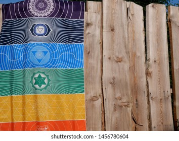 This image depicts a chakra tapestry hung over a wooden fence. The aura-colors on the chakra tapestry function as a meditation aid for a yoga, tantra, buddhist & hinduist meditation practice.
