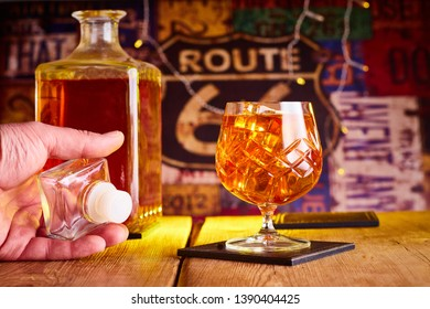 This is a image of a glass of brandy with a decanter along side it ,also there is a hand holding the decanter top, plus there is a colourful background with some bokeh in the image.
