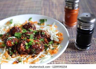 This is a image of Manchurian dry stater decorated with Soya sauce and Red chilli sauce