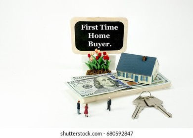 This image of miniature people buying a home, depicts money for a mortgage loan on a white background. A realtor is talking to prospective home home buyers, about closing costs and financial planning.