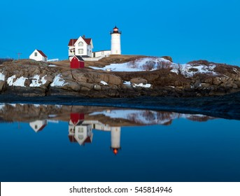This is an image of the Nubble Light in York, Maine taken during a Winter twilight.  A reflection of the lighthouse can be seen in a puddle.  The lighthouse is also known as the Cape Neddick Light.