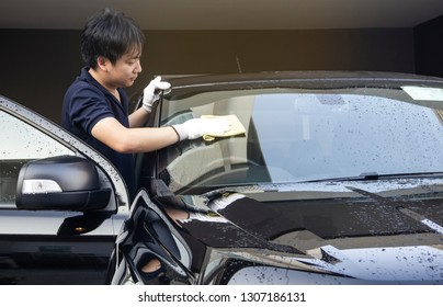 This image is a picture of wiping the car by a yellow microfiber cloth with hand wearing gloves.Car wash concept.