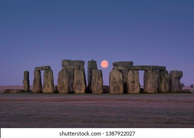 This image shows the ancient stones of Stonehenge with glowing moon between megaliths, Wiltshire, England