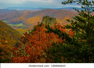 This image shows climbers at the top of a in Monongahela National Forest in West Virginia. In the distance are Autumn tinged mountains with the green valley below.