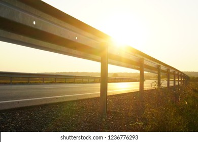 This image shows a highway at sunset. In the foreground you can see a guardrail.
