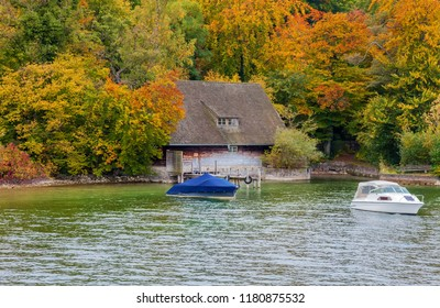 This image shows a hut in autumn with boats in a sea