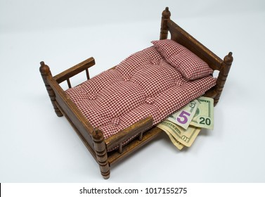 This image shows and old bed with money stuffed under the mattress. It represents the old fashioned way of saving money, and people who don't trust banks.