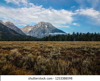 This image shows the Teton Range from a distance. It is located in Grand Teton NP in Wyoming. The Tetons and several small glaciers are seen in the background, and sagebrush is in foreground.