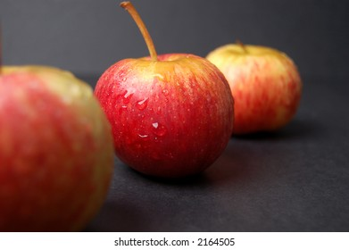 This is an image of three wet apples, nicely compositioned.
